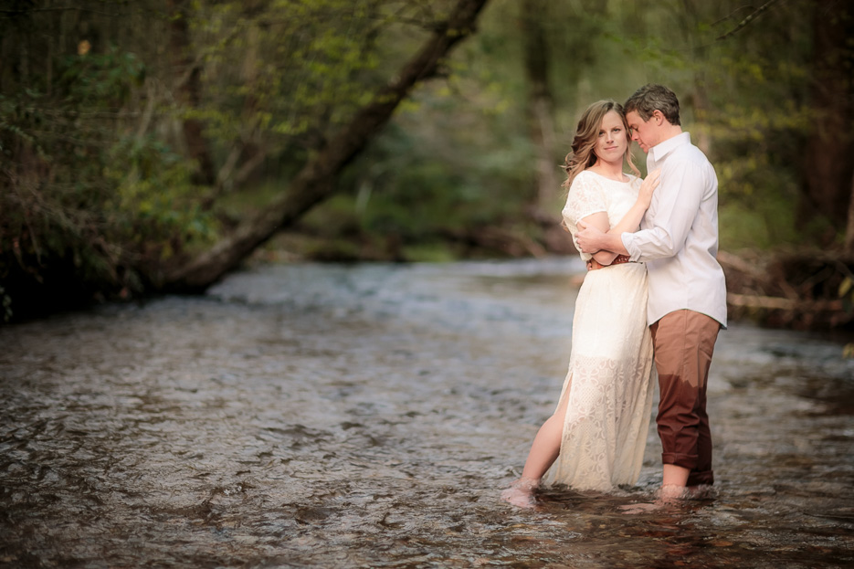 Couple embracing each other standing in a river at the Pisgah National Forest in Ashville, NC