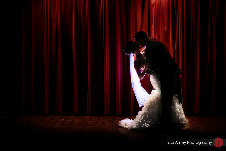 backlit bride and groom embrace against red theater curtain at lux Grandover Resort wedding in Couture Olia Zavozina Gown in Greensboro, NC