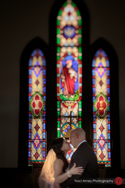 bride and groom share kiss in front of intricate stained glass windows in St. Athanasius Church, Burlington, NC