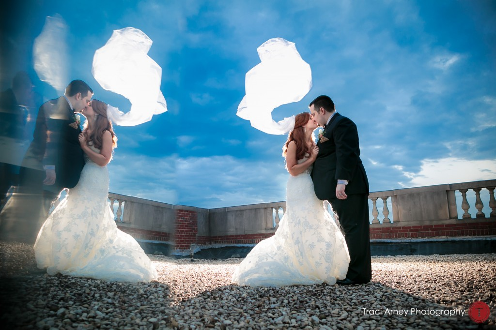 Mirrored bride and groom with backlit veil and blue skies at their wedding at Millennium Center in Winston-Salem, NC.
