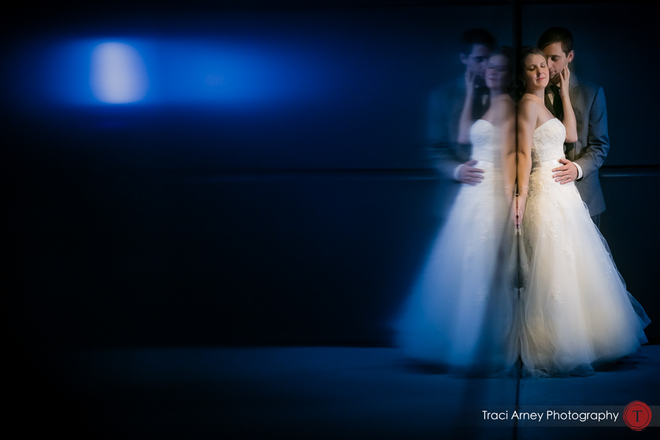 bride and groom embrace in blue lit hallway at baseball stadium